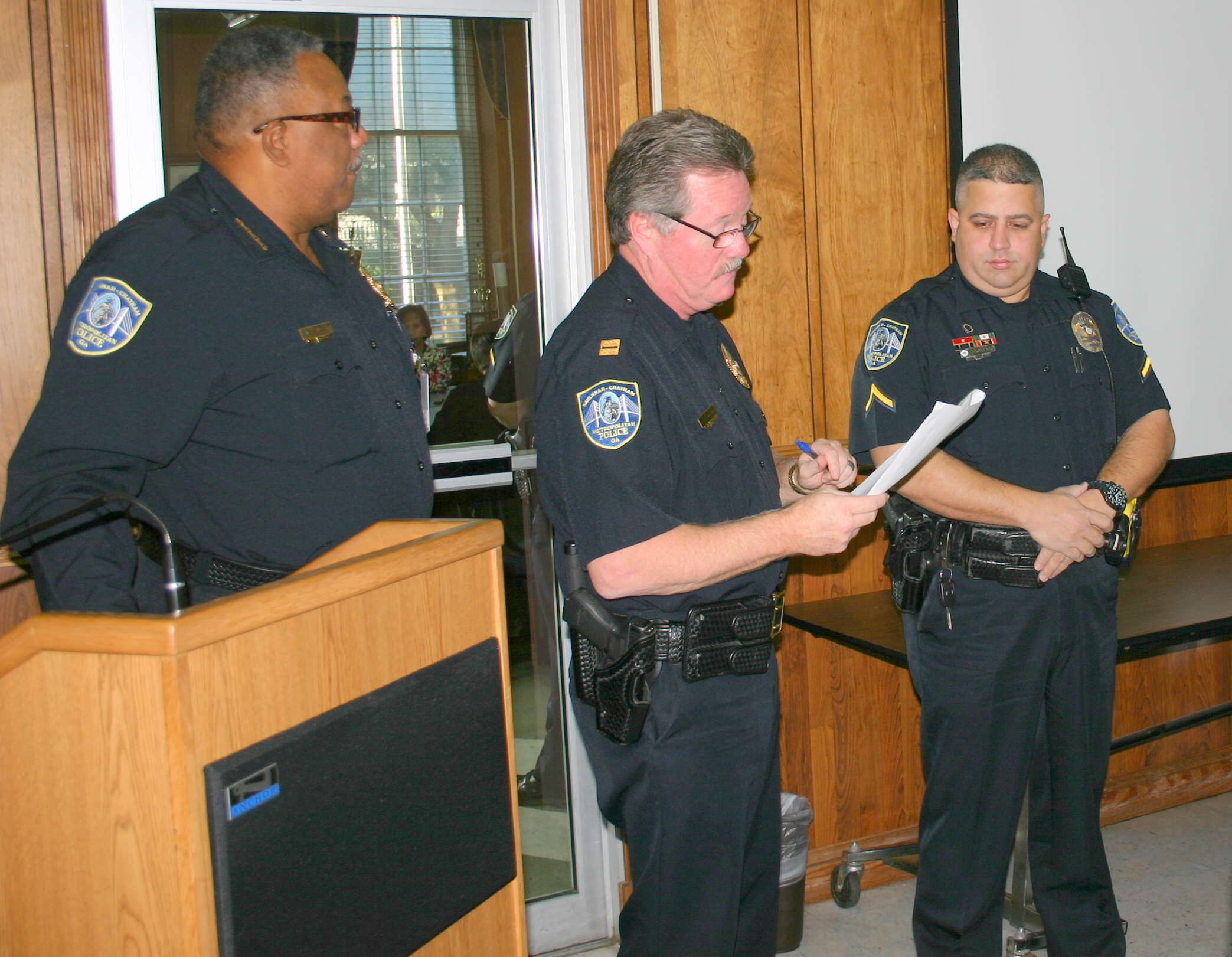Photo 2 caption: Chief Willie Lovett, Capt. Philip Reilley present T-shirt to Officer Jason Pagliaro