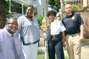 Mobility and Parking Services Assistant Director Leonard Bostick Director Veleeta McDonald Police Chief Julie Tolbert Sgt  Eddie Grant display new signs.